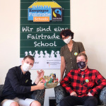 Schpler vor dem Fair Trade School Logo.